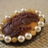Brosa Doamna de ciocolata; realizata pe suport dublu din bumbac vopsit manual in culori combinate, speciale pentru textile; camee foarte frumoasa cu portret ciocolata pe fond galben intens, incadrata de perle ivoire si margele de jad galben, toate cusute manual; dimensiuni: 53X43 mm; o brosa speciala, ce confera un aer misterios si vintage; UNICAT; VANDUTA