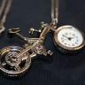 Colier ceas Bicicleta, argintiu vintage; lantul are 46,5 cm lungime (93 cm desfasurat) si este infrumusetat cu perle de sticla roz delicat si perlute de sticla somon; pandantivul-ceas are 65X40 mm; ceasul functioneaza cu baterii; un accesoriu deosebit, estetic si cu functie practica, totodata, care va va scoate din anonimat; VANDUT