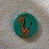 Martisor-pandantiv Girafa vesela, modelat din lut, pictat manual si lacuit, diam. 3 cm